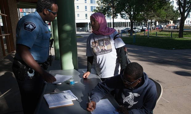 Officer Mukhtar Abdulkadir speaks with a woman who is wearing a Free Our Boys T-shirt in support of five young men recently accused of attempting to join Isis.