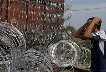 A migrant stares at the closed border crossing between Serbia and Hungary, near Horgos, Serbia, on Tuesday.