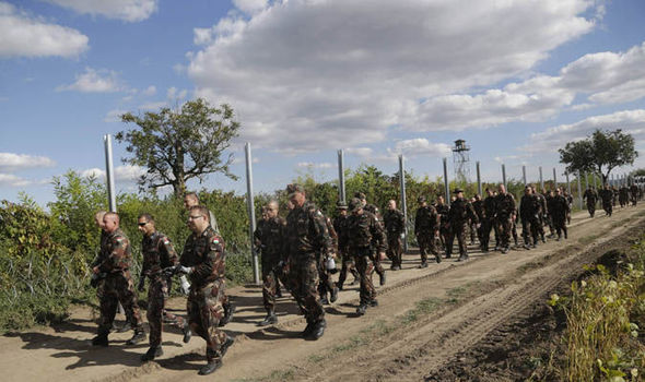 Hungarian soldiers march past the country's barbed wire border fence.
