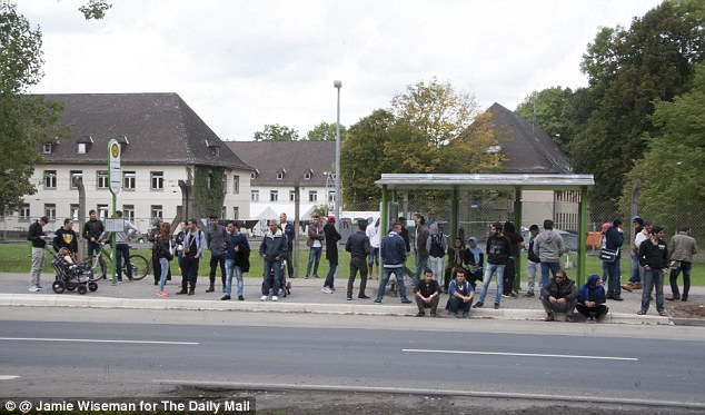 Migrants and refugees pictured waiting for a bus outside the Migrant Receiving Camp on the outskirts of the German city of Giessen.