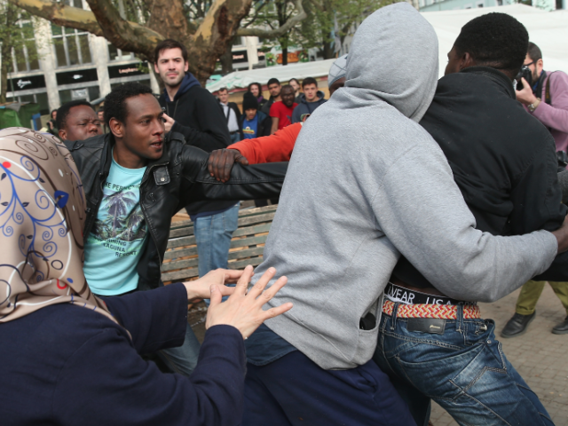 Middle Eastern migrants spar in Germany while journalists snap pictures.