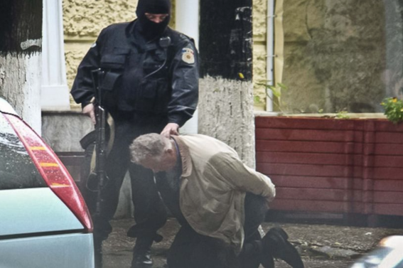 A man is detained by a police officer in Chisinau, Moldova during a uranium-235 sting operation.
