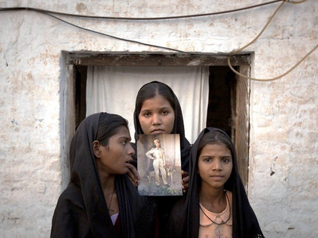 The daughters of Asia Bibi with an image of their mother, standing outside their residence in Sheikhupura, Pakistan in 2010.