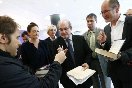 Author Salman Rushdie (middle) signs autographs following the opening news conference of the Frankfurt book fair in Germany earlier this week.