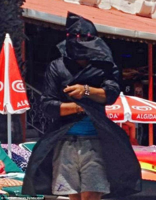 A man reported to be a member of staff at Club Hotel Pineta in Marmaris, Turkey, confronts unsuspecting holidaymakers by the pool while dressed as an ISIS killer in a black hood, mask and robes.