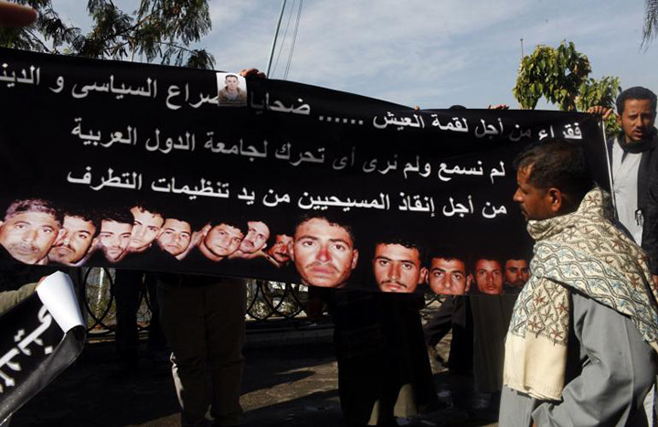 Families of 27 Egyptian Coptic Christians workers kidnapped in the Libyan city of Sirte hold a banner with pictures of their kidnapped relatives as they ask for their release in front of the U.N. office in Cairo in January of 2015.