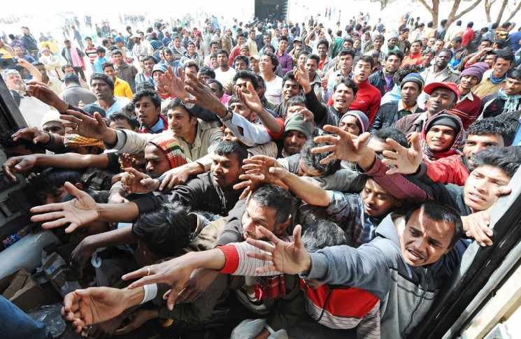 "A crowd of Middle Eastern ""migrants' clamors for entry to Europe early in 2015."