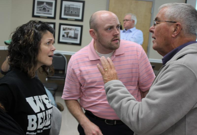 Parents Rachel Presley and Chris Smith, left, express their concerns about the teaching of Islam at their school to School Board Member Bill Robinson,