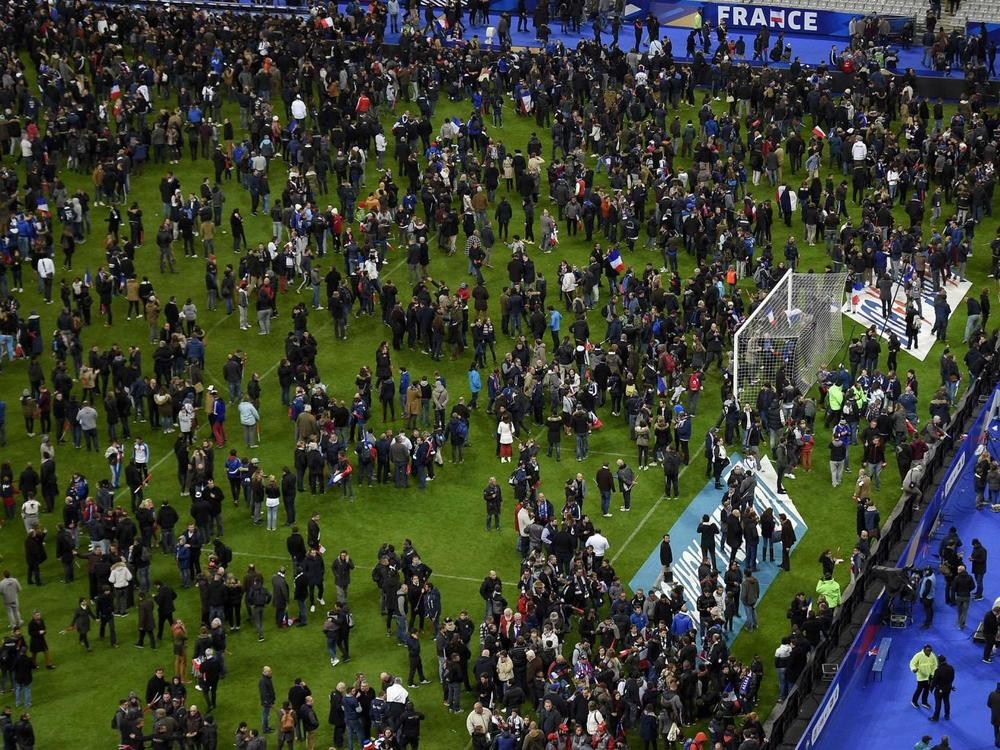 People crowd the field of the Stade de France during the Paris attacks.