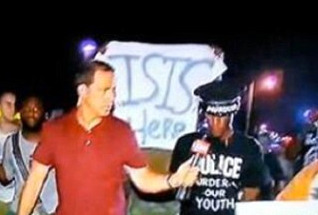 Interestingly, this photo of unrest in Ferguson, Mo. in 2015 shows an ISIS-supporting banner in the background.