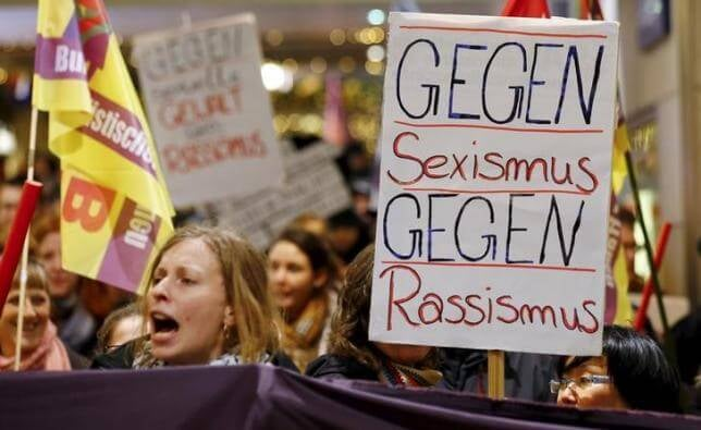 "A sign held by a female protester in Cologne on Jan. 5 reads: ""Against Sexism Against Racism."" If opposing sexual assault is to be called racism, what is to be done?"