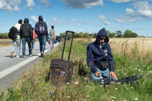 A migrant prays on the side of a road as a large group walks on a highway toward Sweden in September.