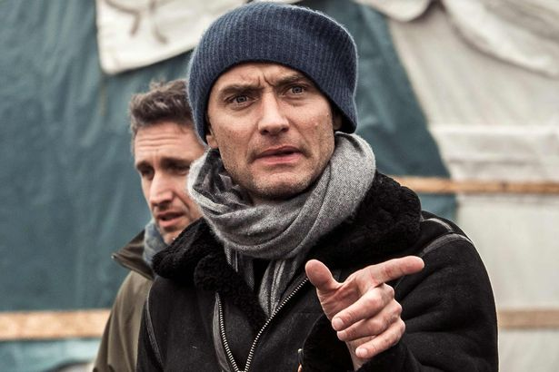"British actor Jude Law gestures during a visit to the ""Jungle"" migrant camp in Calais."