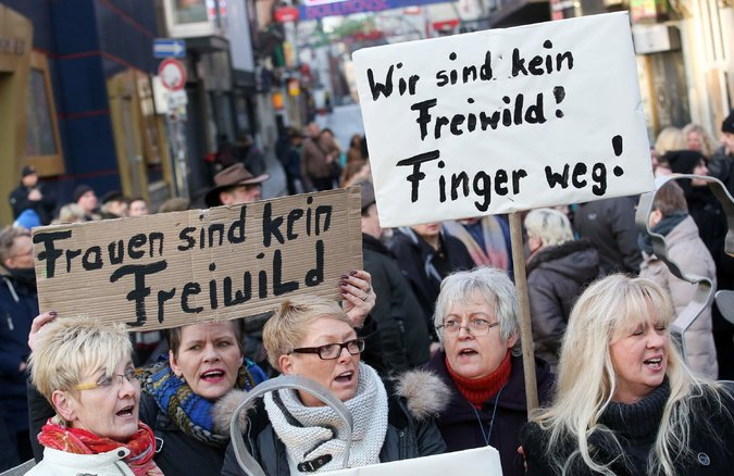 "Women protest in Cologne earlier this year, holding signs saying ""Women are not free game"" and ""hands off."""