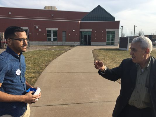 Shiab Mussad, 22, left, a Sanders supporter, speaks with Ahmad Musaad, 76, a Clinton supporter, outside a polling place in Dearborn, Mich. on March 8.