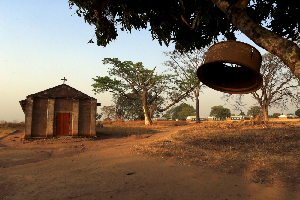 A church bell hangs from a tree brunch outside a Catholic church and school in Odek, Uganda.