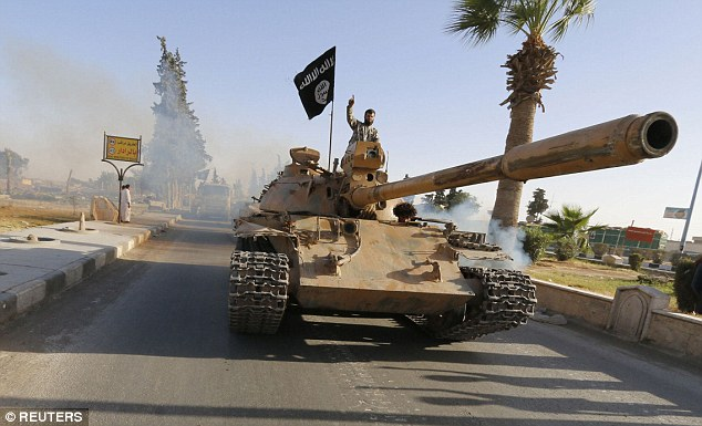 An ISIS fighter waves from a captured government tank in Syria.