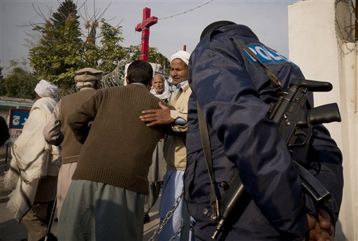 People from the Pakistani Christian community leave a local church under security after attending Christmas Mass last year.