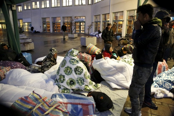 Refugees sleep outside the entrance of the Swedish Migration Agency's arrival center for asylum seekers at Jagersro in Malmo, Sweden, last year.