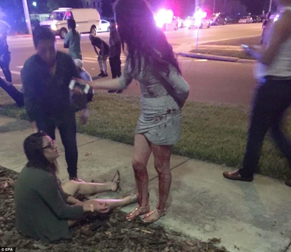 A woman sits on the ground outside the club while another party-goer, whose legs are covered in blood, stands beside her.