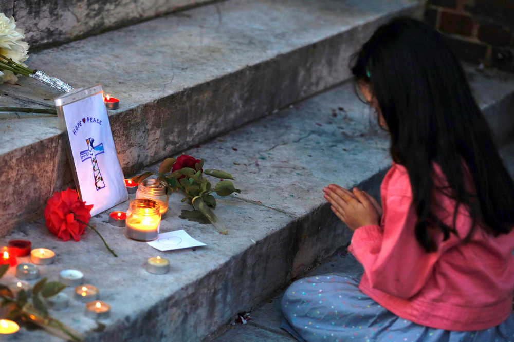A girl prays in front of flowers and messages displayed in front of the city hall of the Normandy city of Saint-Etienne du Rouvray on July 26, 2016 in tribute to the priest killed in the city's church.