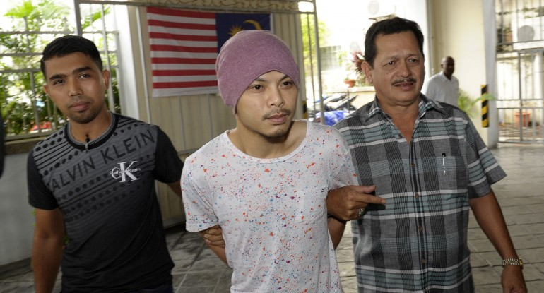 Wee Meng Chee, center, a Malaysian rapper popularly known as Namewee, is escorted by plainclothes policemen as he arrives at the magistrate court in Penang, Malaysia, on Monday.