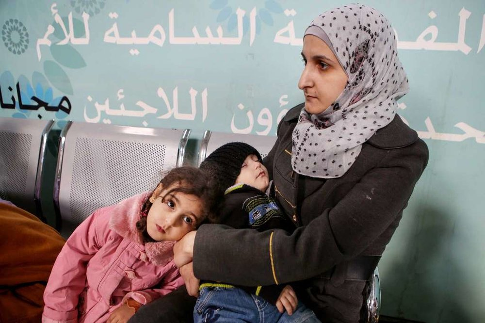 A Syrian woman and children wait at the registration office at the headquarters of the U.N. refugee agency in Amman, Jordan.