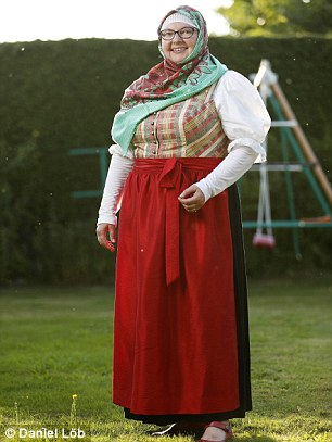 Renate Hoffmann (above) has created her own version of the traditional Bavarian dirndl (pictured below right). Gone is the low cut top and now it comes with a Muslim-style headcovering