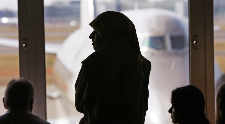 A passenger at Heathrow Airport outside London waits in her hijab.