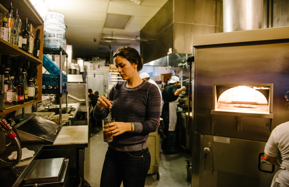 Rachel Astin, general manager of Eva's, mixes a drink in the kitchen, out of customer's sight