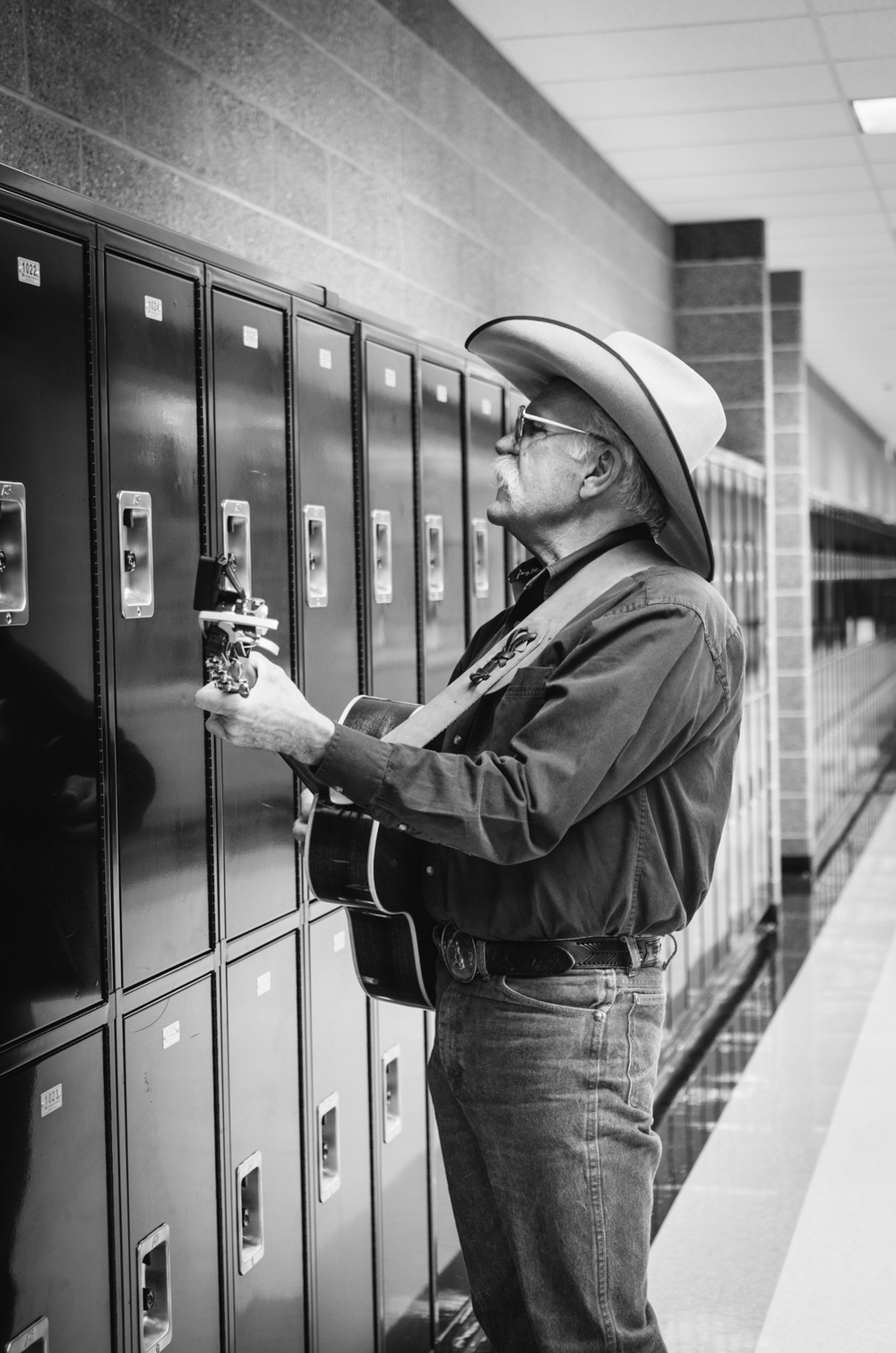 In the bustling Wasatch High School, a performer warms up by listening to the echo of his voice and guitar off of lockers.