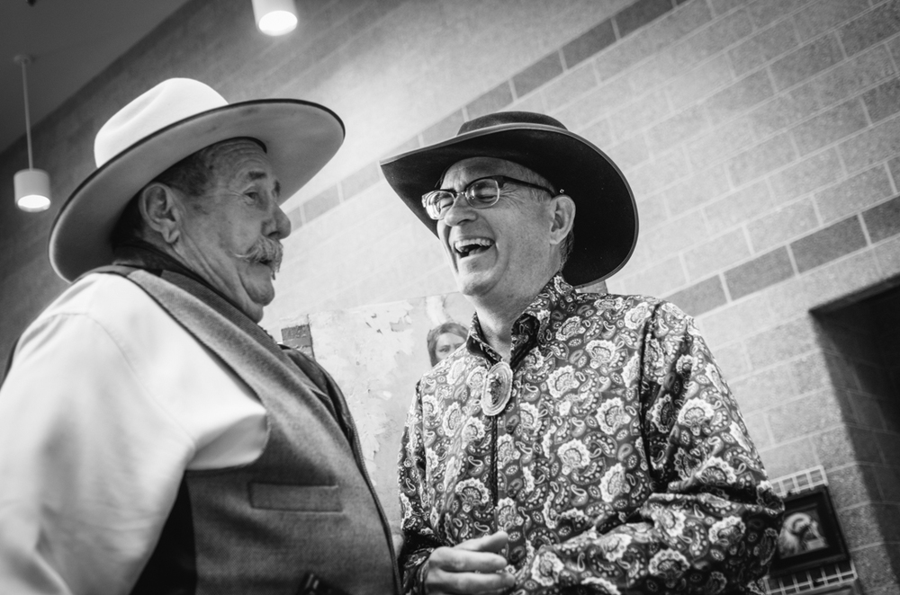 A couple of cowboys share laughs in one of the hallways.