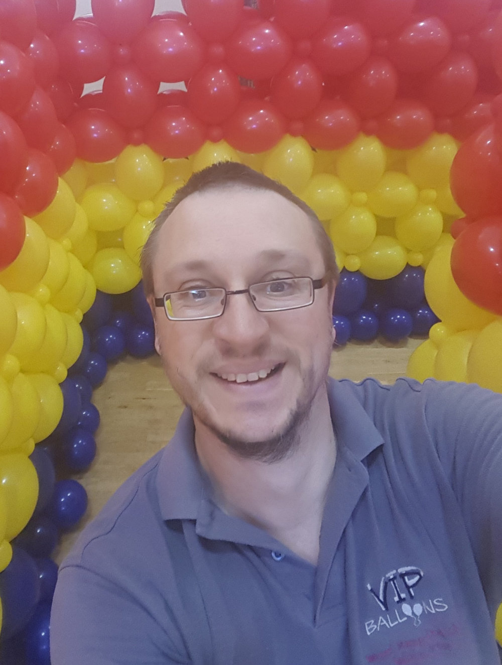 Balloon artist Samuel Stamp-Dod with a balloon wall