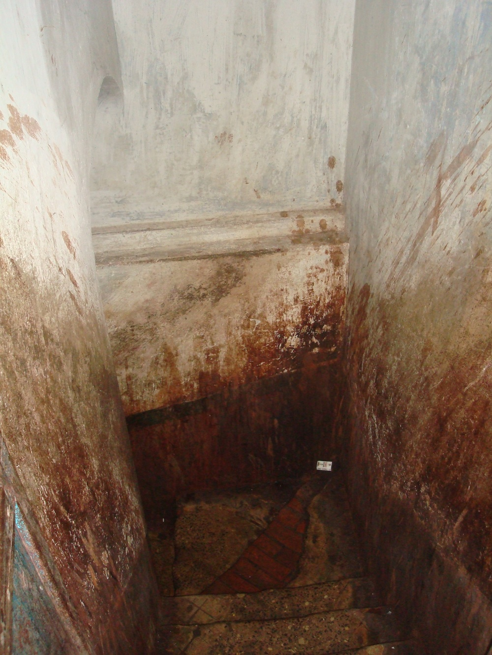 The stairwell of a brothel covered in spit and filth.