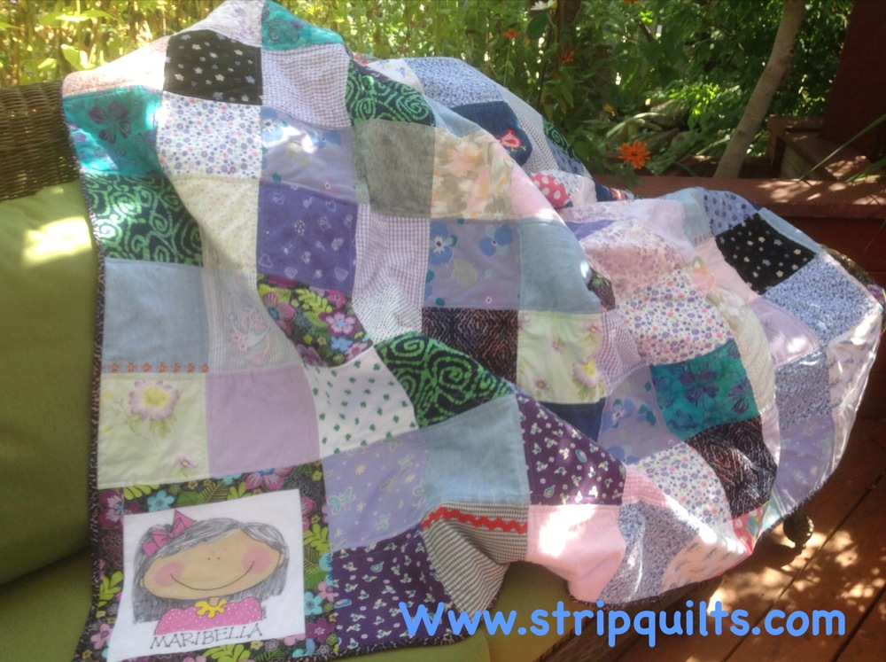 This quilt was made with Maribella's baby clothes that her mother saved for years.  The clothing was cut into 8 inch squares.  I added some fabric from my own stash to give it more contrast.