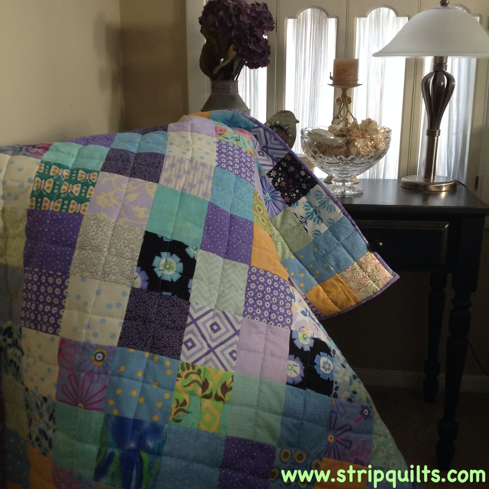 I started and finished this quilt this week.   Waiting for new fabric to arrive, I dipped into my square bin to pull out charms and layer cakes in shades of purple green, yellow and blue.  The back is done in a solid robin's egg blue.