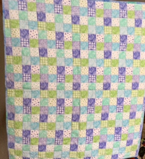 Checkered Panel   This quilt is a flannel panel. The size is 38 x 43. The binding is a tie die print. The back side is a small green polka dot print. Sale price is $39.00.