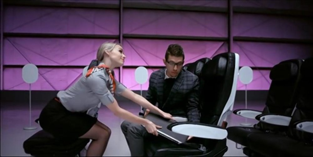 When a dancer tries to store his laptop in an empty seat, an air hostess lets him know that this is not FAA-recommended behavior. (VIRGIN AMERICA)