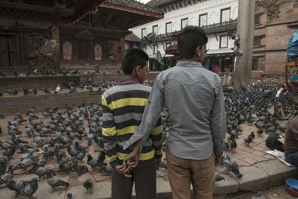 Two men stand in front of the partially damaged Kal Bairam temple in the Darbar Square area in Kathmandu, April 27, 2015.