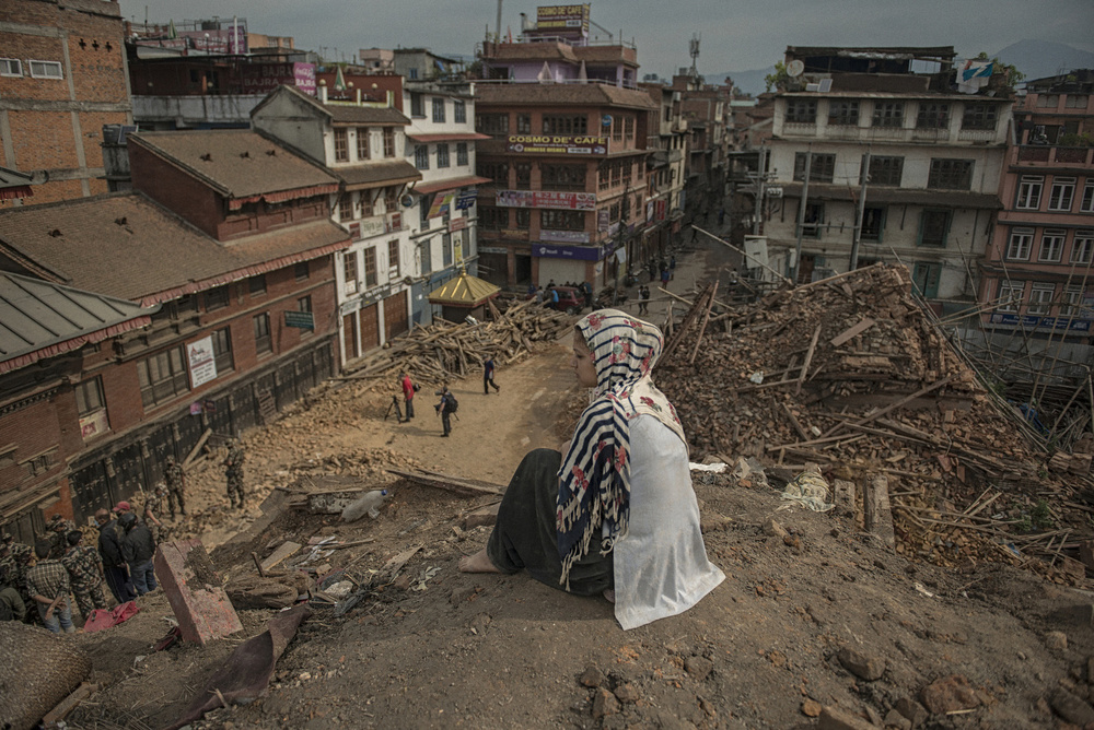 Shangita sits on top of a broken temple in Darbar Square, April 29, 2015. She owned a shop near the temple which is now under the rubble.