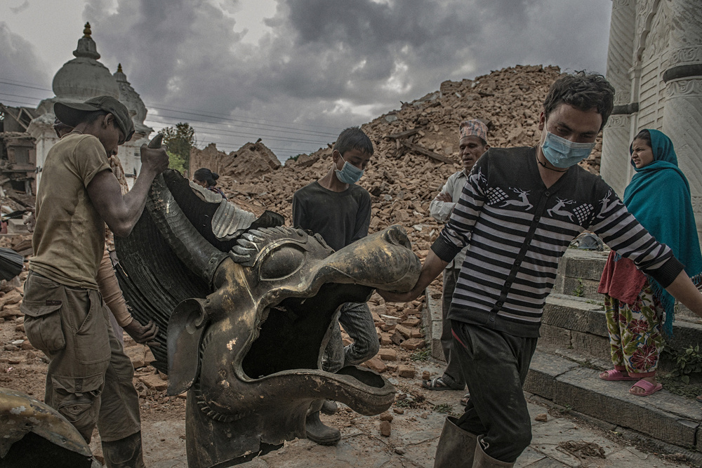 Broken parts of Ram Narayan Temple are carried by volunteers to a safe place in Kathmandu, April 29, 2015.