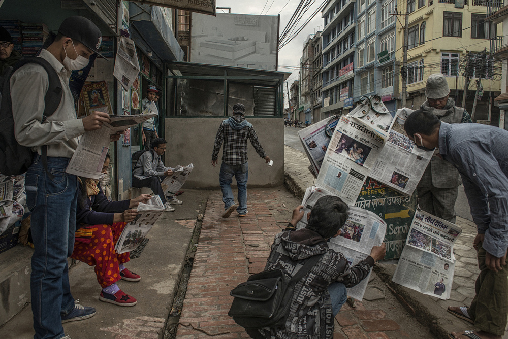Newsstands are open again after closing for five days after the earthquake. Everyone is reading about the earthquake.