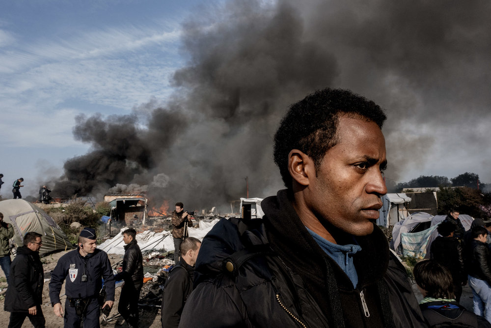 26th October 2016, The Jungle of Calais in France is in huge fire. A migrant leaves his camp.