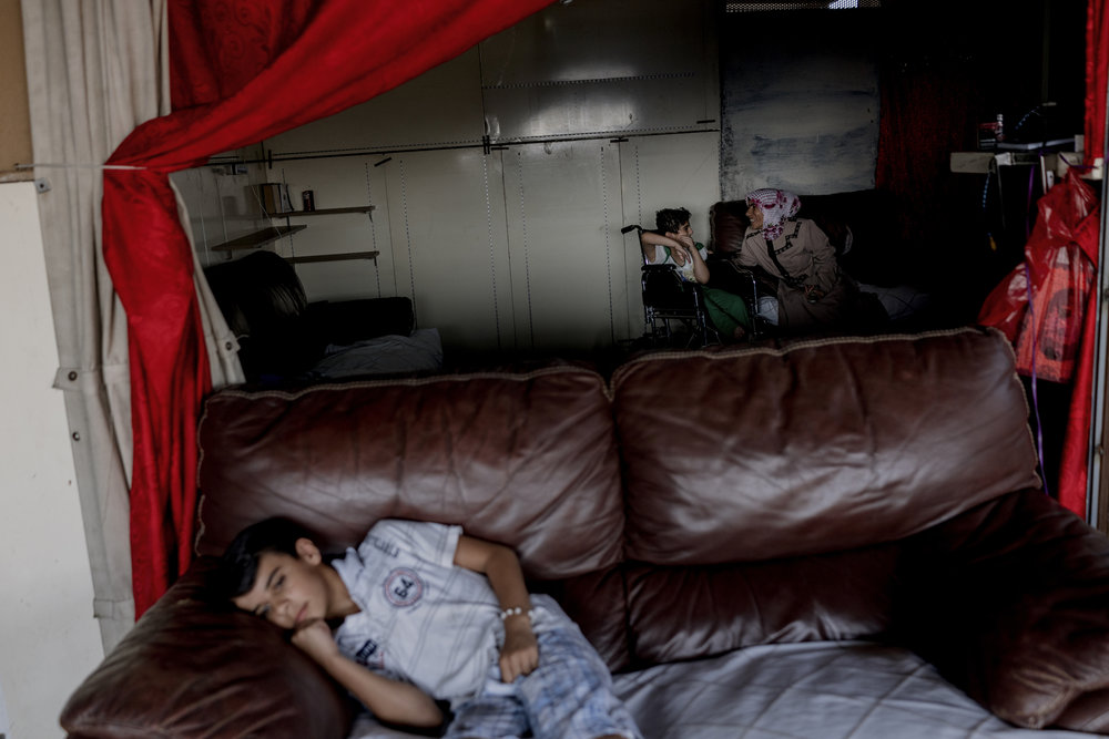 A Syrian refugee boy,  Mustafa elder brother of Sindos and Tamim lays on the couch in their makeshift living space on the rooftop of an industrial building in Beirut. His sister Sindos is suffering from a severe degree of cerebral palsy and epilepsy and brother Tamim  was also diagnosed with moderate cerebral palsy (lower degree than Sindos, his older sister).