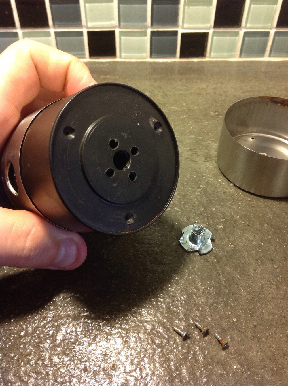 Buy a 1/4-20 T-nut from your local hardware store. This is the same thread as a standard tripod base. Line up the T-nut with the center of the timer. Drill a large hole in the center of the plastic timer body, then drill four smaller holes around it that will line up with the spikes on the T-nut.