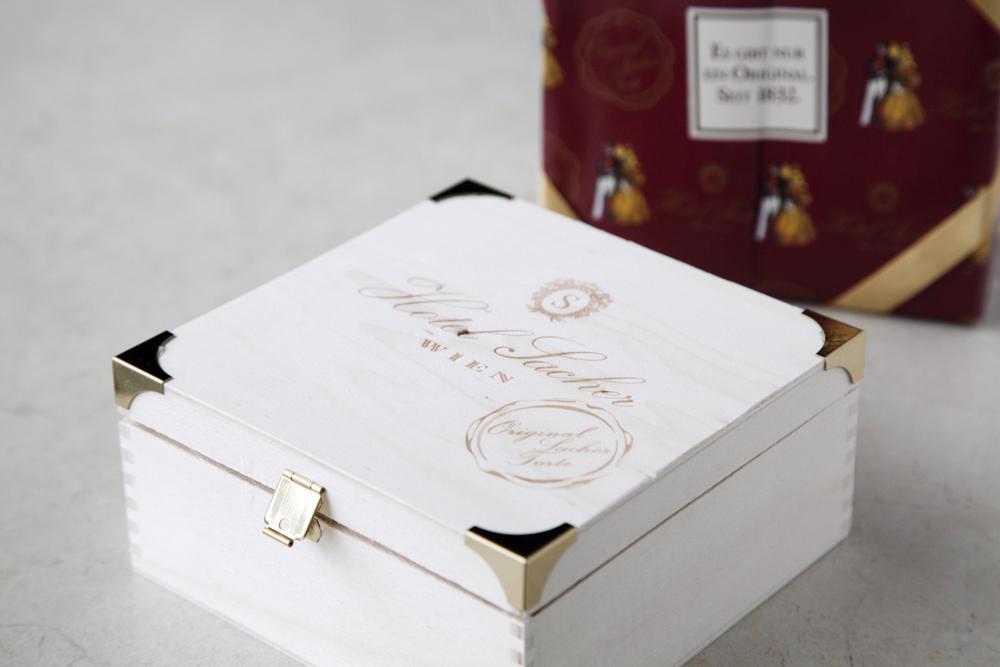 拆開印有18世紀貴族男女的堂紅包裝紙、接著打開白色木盒,是一顆印有圓形封章的巧克力蛋糕。帶著濃稠的可可色、淡淡的苦甜香氣、平滑緻密的甘納許淋面,這顆蛋糕的一切都能擄獲巧克力狂熱者的心。