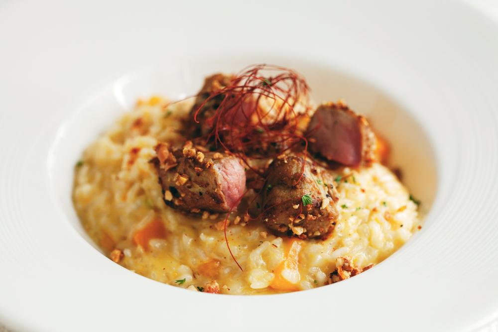 【南瓜燉飯佐堅果小牛】 燉飯在最後烹煮階段拌入各種油脂,使風味口感更富層次的動作有個專有名詞–「Mantecare」。舉凡奶油、各式乳酪或是橄欖油都是選擇之一,基本原則是,口味濃厚的肉類燉飯搭配動物油脂,魚類或菜蔬類燉飯則可以加入橄欖油。