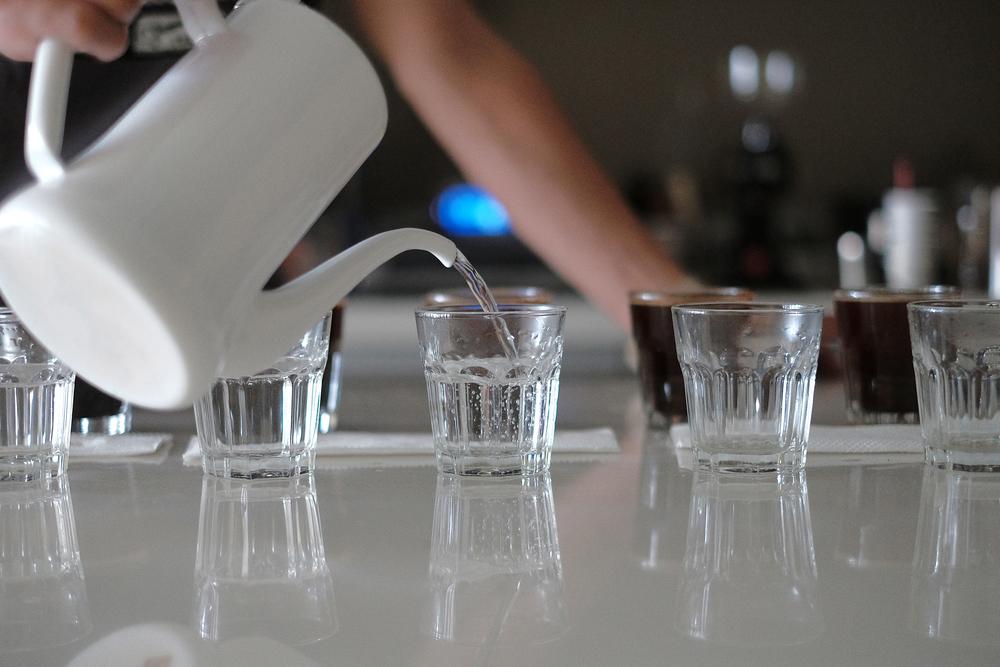杯測時,我們會在每杯咖啡豆前擺好一杯熱水,用來洗潤咖啡匙以免每杯咖啡的風味互相混雜影響咖啡師的判斷。