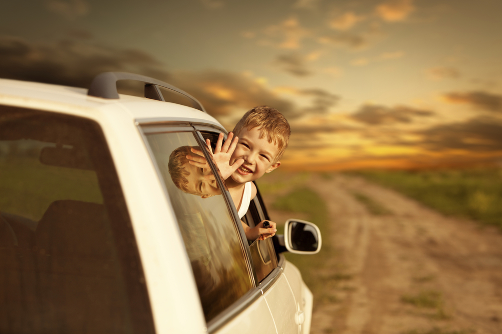 stock-photo-14531197-child-looking-out-the-window-and-waving-from-white-car.jpg