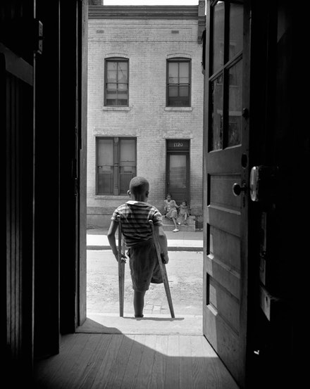 Gordon Parks,  Washington, D.C. Young boy standing in the doorway of his home on Seaton Road in the northwest section. His leg was cut off by a streetcar while he was playing in the street, June 1942.  Gelatin silver print, printed later. 20 x 16 inches. © and courtesy The Gordon Parks Foundation.